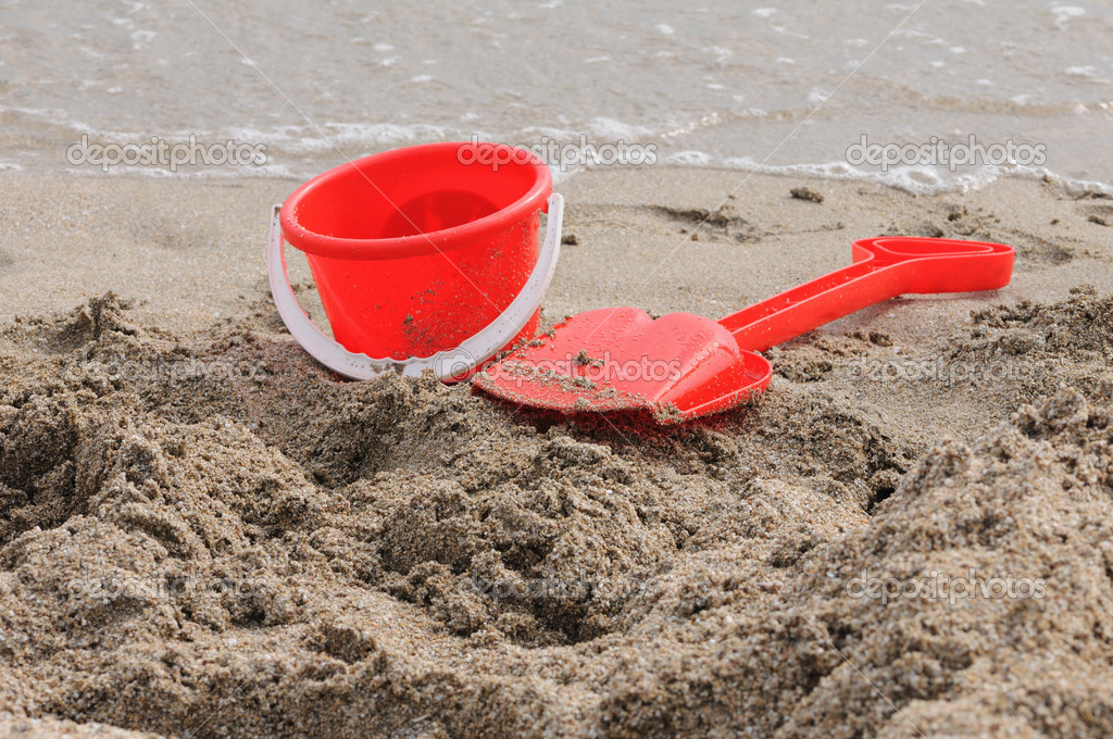 Red Sand Pail and Shovel on a beach — Stock Photo #3631502