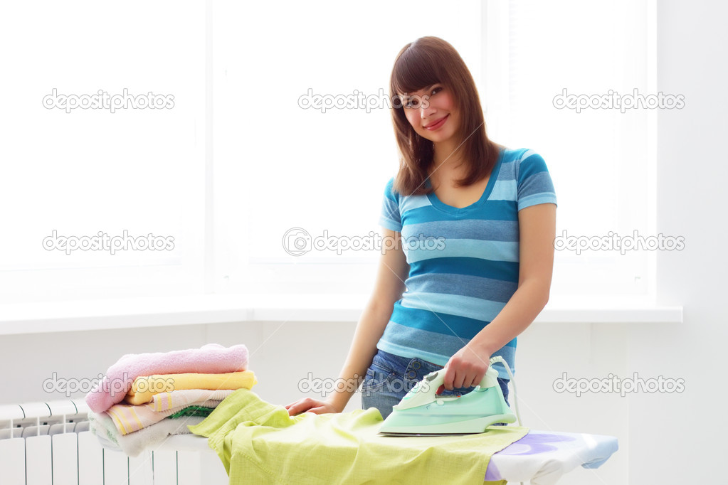 Young woman ironing on a light background — Photo #2692863