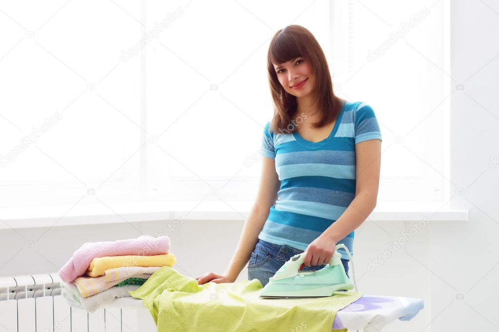 Young woman ironing on a light background — Stockfoto #2692863
