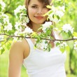 Beautiful girl about to apple tree — Stockfoto