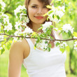 Beautiful girl about to apple tree — Stock Photo