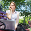 Business woman sitting on a bench - Stok fotoğraf