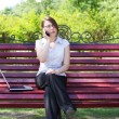 Business woman sitting on a bench — Stok fotoğraf