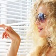 Attractive girl looks out the window — Stock Photo