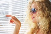 привлекательная девушка смотрит в окно — Стоковое фото