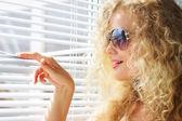 Jolie jeune fille regarde par la fenêtre — Photo