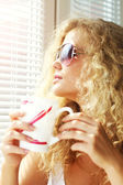Beautiful girl near the window with a cup — Stock Photo