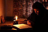 Man sitting by candlelight — Stok fotoğraf