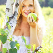 Beautiful girl holding green apple — Stock Photo