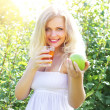 Beautiful girl is holding an apple and juice — Stock Photo #3543641