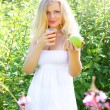 图库照片: Beautiful girl is holding an apple and juice