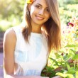 Stock Photo: Beautiful girl in a flowered garden