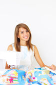 Girl and a sewing machine on a light background — Stock Photo