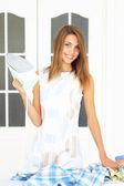Beautiful girl next to ironing board — Stock Photo