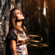 Dreamy girl standing next to a tree — Stock Photo