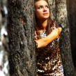 Dreamy girl standing next to a tree — Stock Photo #3748388