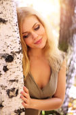 Attractive girl standing at the birch — Stockfoto