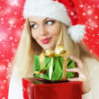 Santa girl holding gifts — Stockfoto