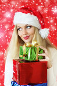 Santa girl holding gifts — Stock Photo