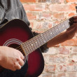 Playing on acoustic guitar — Stockfoto