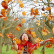 Woman throwing leaves — Stock Photo