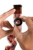 Ruka držící zvětšovací sklo a film — Stock fotografie