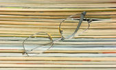 Glasses and stack of magazines — Стоковое фото