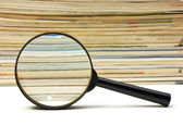 Magnifying glass and stack of magazines — Stock Photo