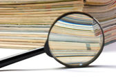 Magnifier and stack of magazines — Stock Photo