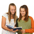 Two teenage girls smiling and reading book — Stock Photo #3799553