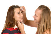 Two teenage girls dye their eyelashes — Stock Photo