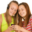 Royalty-Free Stock Photo: Two teenage girls listening to music on your mobile phone