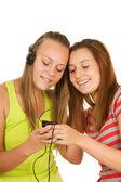 Dwóch nastoletnich dziewcząt, słuchanie muzyki w telefonie komórkowym — Zdjęcie stockowe