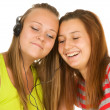 Two teenage girls listening to music on your mobile phone — Stockfoto