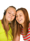 Two teenage girls listening to music on your mobile phone — Stock Photo