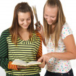 Two teenage girls smiling and reading book — Stock Photo #3842205