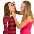 Stock Photo: Two teenage girls dye their eyelashes