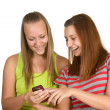 Portrait of lovely young women using mobile phone together — Stock Photo