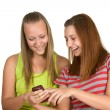 Portrait of lovely young women using mobile phone together — Foto Stock