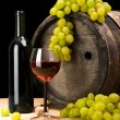 图库照片: Red wine and green grape on a background of old wine barrel