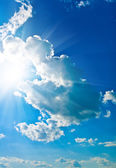 Brightly cloudy sky and sun — Stock Photo