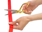 Hands of woman with scissors and red line isolated — Stock Photo