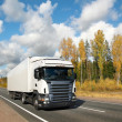 White truck on autumn country highway - Stock Photo