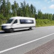 White mini bus speeding on country highway, motion blur - ストック写真