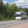 White tourist bus on country highway - Stock Photo