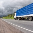 Truck on country highway and stormy clouds — Stock Photo