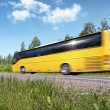 Yellow tourist bus speeding on rural highway, motion blur, with reflecting — Stock Photo
