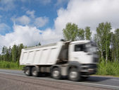 White dump truck speeding on rural highway, motion blur — Stock Photo