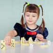 Little girl playing with dominoes - Stock Photo