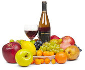 Bottle and glass of red wine among fruit - still — Stock Photo